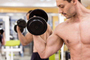 bodybuilder man with a dumbbell in fitness club