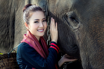 The asian girl took a cane to feed the elephants.