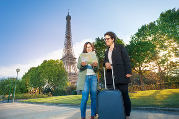 Travelers reading map against the Eiffel Tower
