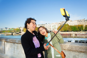 Cheerful tourists taking selfie photo with stick