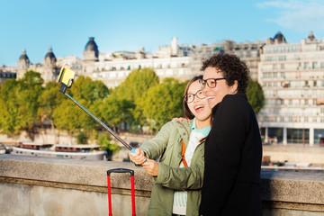 Cute friends taking photo using a selfie stick