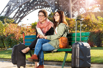 Travelers sitting on bench and holding paper map