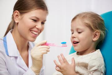 Female hygienist teaching little girl to brush teeth in dental clinic. Dental care concept.