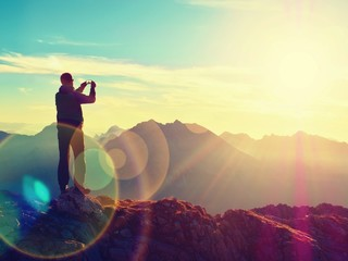 Lens flare. Hiker takes selfie photo. Tourist at peak
