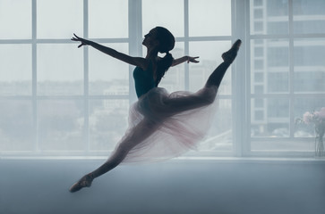 Ballerina in the jump in front of a window