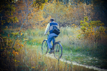 an old man rides a Bicycle through the woods