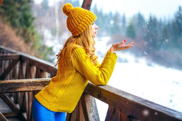 Girl in a sweater and hat catches the snow
