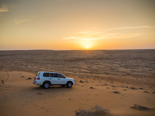 Oman, Al Raka, off-road vehicle parking on dune in Rimal Al Wahiba desert at sunset