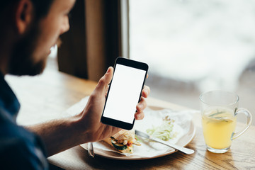 Young man looking at phone, sitting at the restaurant