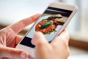hands with gazpacho soup photo on smartphone at restaurant