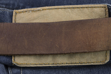 Detail of leather belt on a blue jeans