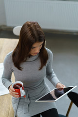 frau sitzt zuhause mit einer tasse tee und liest am tablet