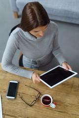 frau sitzt zuhause am tisch mit tablet und handy