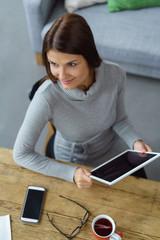 lächelnde frau sitzt zuhause am tisch mit tablet und handy