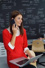 junge frau im büro telefoniert und schaut lächelnd nach oben