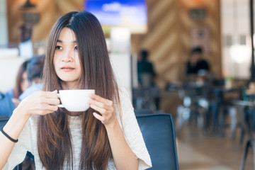 Young charming asian student woman hold cup of coffee drink