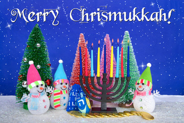 Menorah and  red, pink, green pine trees with snowman on faux snow blue background white dots and stars. Christmas and Hanukkah together. Multi faith celebration. Merry Chrismukkah