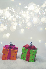 Christmas presents in snow with lights bokeh in background, retro toned