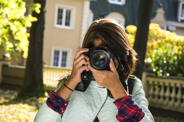 Outdoor lifestyle portrait of a pretty young woman with a camera taking a photo.