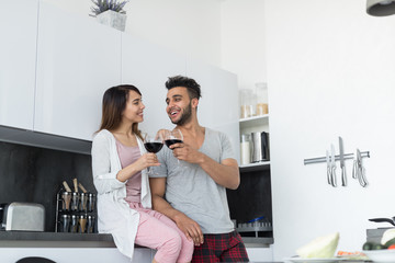 Young Couple Drink Wine In Kitchen, Hispanic Man And Asian Woman Hug Celebration Modern Apartment Interior