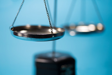 Silver scale of justice on wooden table in blue tone
