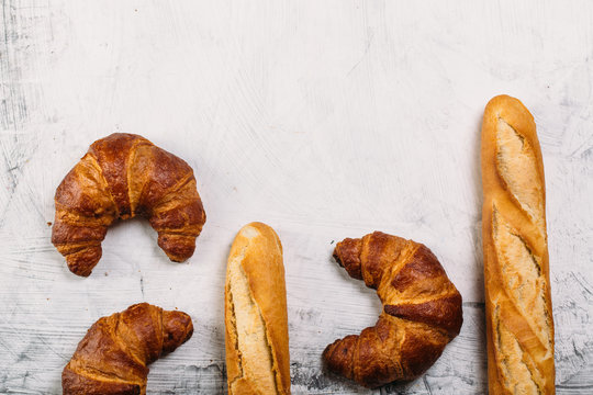 Food background: Freshly baked baguette and croissants on white texture table with copyspace