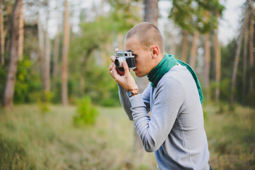 man with retro vintage camera in the forest