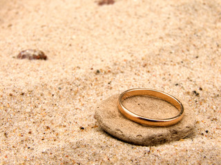 Gold wedding ring on a stone in sand