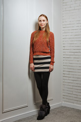 Young positive girl standing near white wall in warm knitted swe