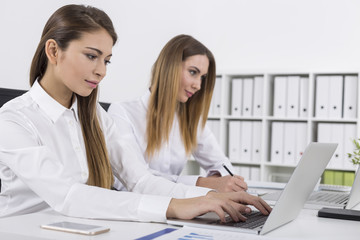 Side view of two women working