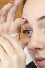 Young woman using eye drops
