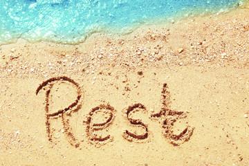 Word REST on beach sand