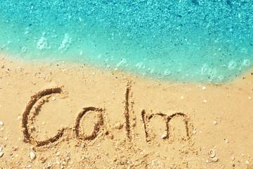 Word CALM on beach sand