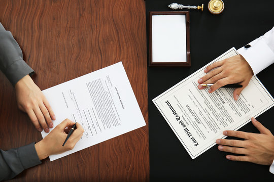 Woman and notary public signing documents