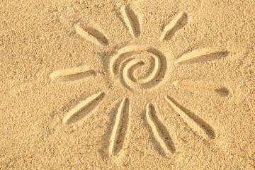 Sun drawn on sea sand, close up view
