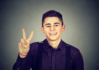 happy teenage guy showing victory or peace sign