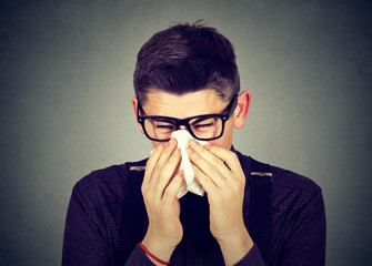 Man in glasses sneezing in a tissue blowing runny nose