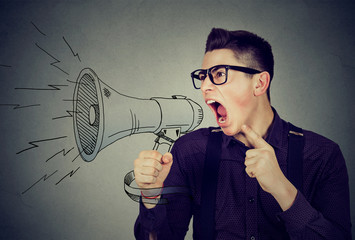 Angry young man screaming in megaphone