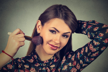 woman applying makeup powder with brush