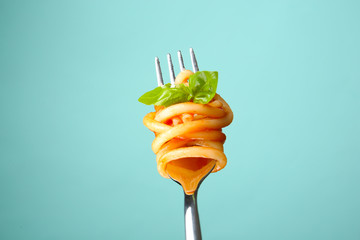 Fork with tasty pasta and basil on color background, close up view