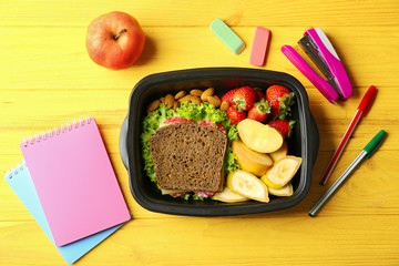 Lunch box with food and stationery on wooden background, top view