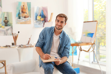 Young male artist drawing sketch in studio
