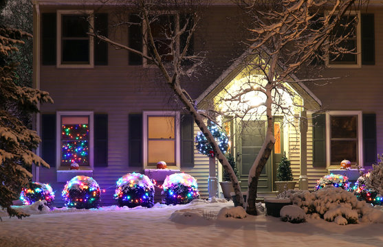Seasonal house outdoors decoration. Background with house front yard, covered by fresh snow, decorated for Christmas and New Year Holidays. Night scene.