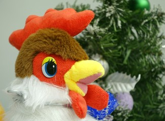 Rooster is a symbol of 2017. Decoration toy on a Christmas background.