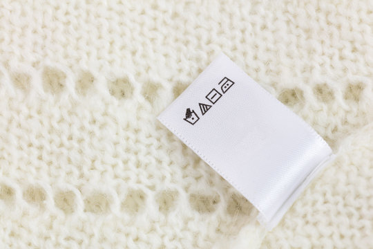 Laundry tag on white knitted wool sweater background