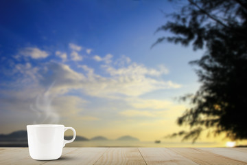 Hot coffee cup with steam on wooden table top on blurred blue sky and beach during sunrise