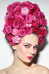 Young beautiful woman with stylish make-up in fancy vintage style wig of pink roses