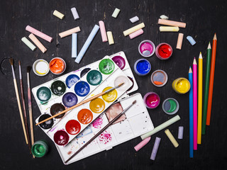 Bright multi-colored paint, pastels, crayons, pencils, brushes on a black wooden background. Set for the artist. Education.
