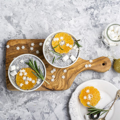 Chia Pudding for breakfast with tangerines, sugar snowflakes and rosemary. Examples of festive winter snack. Top view.