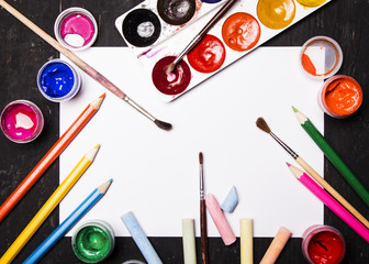 Bright multi-colored paint, pastels, crayons, pencils, brushes on white sheet and black wooden background. Set for the artist. Education.
